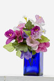 Decorative traditional blue bottle. With fake flowers in it at Santorini island, Greece Royalty Free Stock Photo
