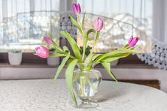 A decorative tulip bouquet on a table. A decorative tulip bouquet on a dining room table cloth Royalty Free Stock Photography