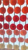 Decorative umbrellas fragment. Red pink orange and white decorative installation made of hanging umbrellas fragment Stock Photos