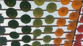 Decorative umbrellas. Green and yellow decorative installation made of hanging umbrellas fragment Royalty Free Stock Photos
