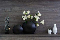 Decorative vases and flowers at dark wooden shelf Stock Photos