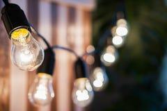 Decorative vintage edison light bulbs against striped wooden wall background. Retro lighting decor stock image