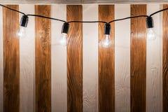 Decorative vintage edison light bulbs against striped wooden wall background. Retro lighting decor stock photos