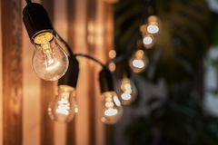 Decorative vintage edison light bulbs against striped wooden wall background. Retro lighting decor royalty free stock images