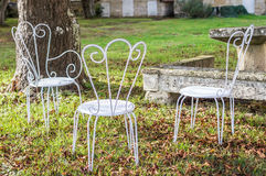 Decorative vintage metal white chairs furniture in a garden. In France Royalty Free Stock Photography