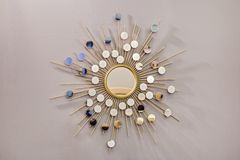 Decorative wall round mirror in the shape of the sun, a golden cooper mirror, modern shape in the Scandinavian style.  royalty free stock photo