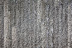 Decorative wall with stone grey vertical rough stone blocks texture outside a building. Architectural details stock photo
