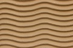 A decorative wall with a wavy structure painted in beige. As a background Stock Image