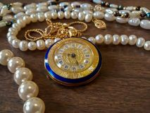 Decorative watch necklace, with gold interface and roman numbers. This is a decorative watch on a chain, with pearl necklaces in the background. The watch has a stock photos