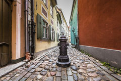 Decorative water column in narrow medieval street of old Riga ci Stock Photo