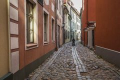 Decorative water column in narrow medieval street of old Riga ci Royalty Free Stock Image
