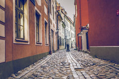 Decorative water column in narrow medieval street of old Riga ci Stock Photos