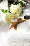Decorative wedding or anniversary gift. With a golden bow lying beside two pure white roses on a linen covered tabletop Royalty Free Stock Photos