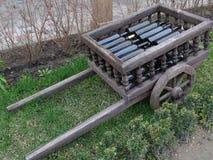 Decorative wheelbarrow with wine bottles. Green grass, decoration, decorative, wooden, interior, design, retro, vintage Royalty Free Stock Image