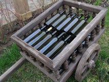 Decorative wheelbarrow with wine bottles. Wood, design, interior, cafe, decoration Royalty Free Stock Photos
