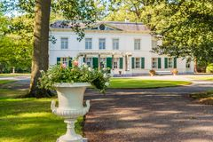 Decorative white flower box with flowering plants in the foregro. Und of the historic Dutch manor Wallsteyn, built in 1810 near the village Achtmaal royalty free stock photos