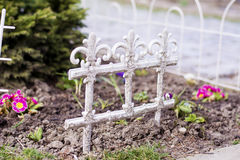 Decorative white metal fence in spring garden stock photo