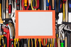 Decorative white page on background of lined up work tools. Stock Images