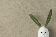 Decorative White Painted Easter Egg Bunny with Drawn Cute Kawaii Face. Green Leaves Ears. Beige Linen Fabric Background. Spring Holiday Crafts Kids Concept stock photo