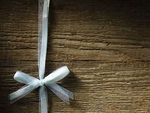 Decorative white ribbon and bow over wooden background Stock Photography