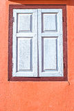 Decorative white window on an old orange stucco wall Stock Photo
