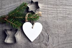 Decorative white wooden Christmas heart and fir tree branch on old wooden background.Winter holidays,Merry Christmas,Happy New Yea. R concept.Selective focus Royalty Free Stock Photo