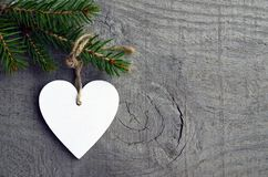 Decorative white wooden Christmas heart and fir tree branch on old wooden background.Winter holidays concept. Selective focus Stock Photo