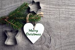 Decorative white wooden Christmas heart and fir tree branch on old wooden background.Winter holidays,Merry Christmas.Selective foc. Us Stock Image