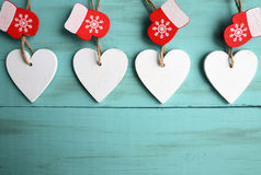 Decorative white wooden Christmas hearts and red mittens on blue wooden background with copy space. Stock Photo