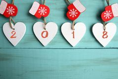 Decorative white wooden Christmas hearts and red mittens with 2018 numbers on blue wooden background with copy space.Happy New Yea