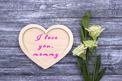 Decorative white wooden heart on grey wooden background with lettering Happy Mother`s Day.