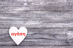Decorative white wooden heart on grey wooden background with lettering Love in Greek.