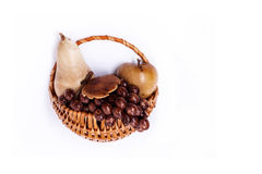 Decorative wicker basket with carved wooden fruit on white background Stock Photo