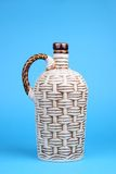 Decorative wicker jug. Decorative ceramic wine jug looks like wicker isolated on blue Royalty Free Stock Image