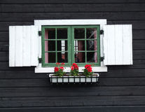 Decorative window of wooden cabin. Old wooden house in Norway. Decorative window with flowers Stock Photo