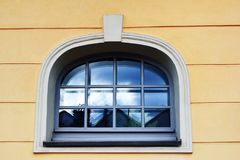 Decorative window on yellow facade. Decorative window on yellow plaster facade of old building close up view royalty free stock photo