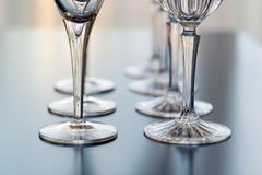 Decorative wine and martini glasses are set up in rows displaying beautiful details of the base of the glass. Wine glasses and martini glasses are set up in rows royalty free stock photography