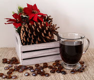 Decorative wood box with pine cones and poinsettia with mug of black coffee Royalty Free Stock Image