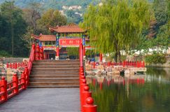 Decorative wooden Chinese gate, architectural arch on the water in Jiangsu Province. Chinese gate architectural arch water pond lake bridge red column stairs Stock Photo