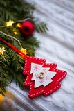 Decorative wooden Christmas tree near fir wreath decorated with red Christmas balls and coiled with glowing garland with warm ligh. T on white knitted plaid. New stock photos