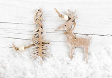 Decorative wooden deer and tree on snow wooden background. Royalty Free Stock Photography