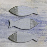 Decorative wooden fishes. Three raised stylistic fishes with identical bodies and tails and silver heads on a square background decorated with faint wavy blue Stock Photo