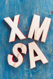 Decorative wooden letters xmas on a blue background, top view Royalty Free Stock Image