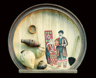 Decorative Wooden Plate. A wooden decorative plate, with an ancient Armenian family drawn on it and small models of  kitchen accessories, used at that time Stock Images