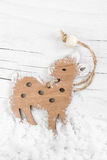 Decorative wooden small deer on the snow wooden background. Royalty Free Stock Photo