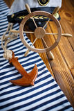 Decorative wooden steering wheel. On an old wooden table Royalty Free Stock Photos