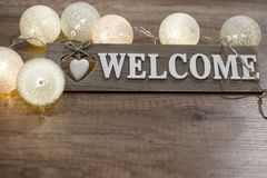 Decorative text welcome with heart and lights on the wooden table. Decorative wooden text with heart and multicolored lights on the wooden table Royalty Free Stock Photo