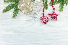 Decorative wool baubles with garland lights and christmas tree b. Ranch on white wooden background stock photography