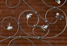 Decorative wrought iron grille. Decorative wrought iron grid in the background of a decorative brick wall stock image
