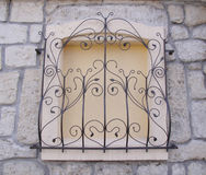 Decorative wrought iron grille on walled window Stock Image